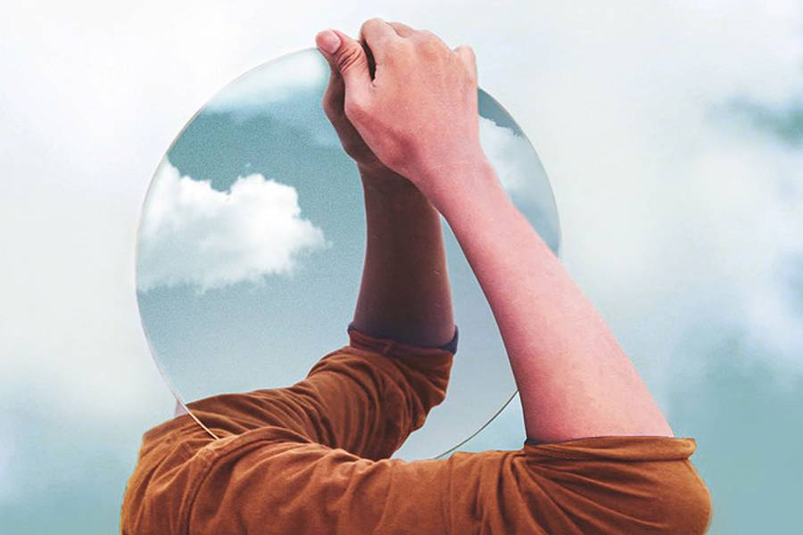 Photoshopped image of a man carrying a round mirror where his head should be
