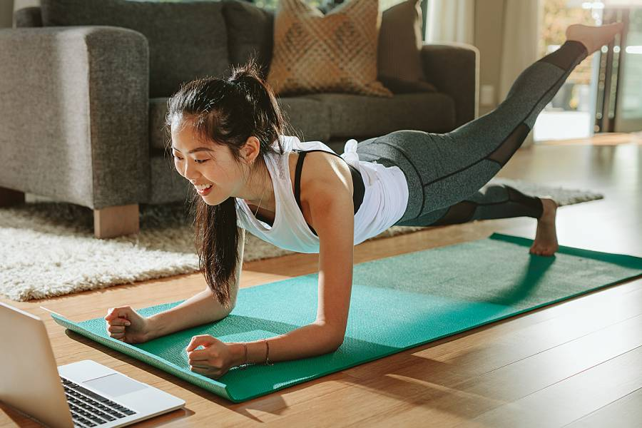 Woman on yoga mat doing a plank exercise while watching a laptop