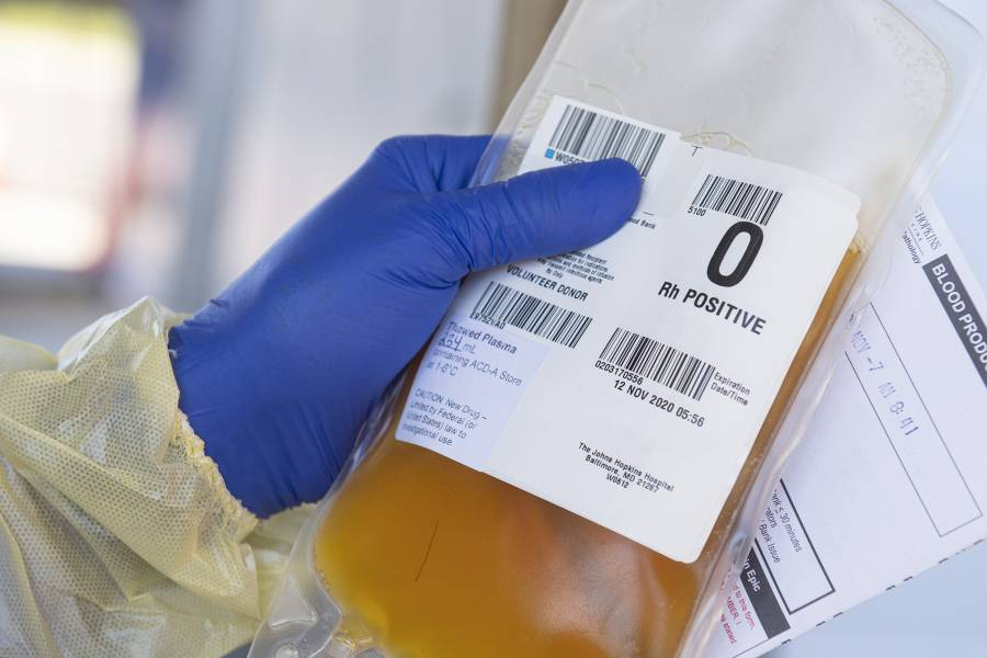 A gloved hand holds a bag of plasma