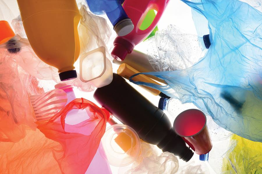 A pile of plastic products, including bottles, cups, and plastic bags