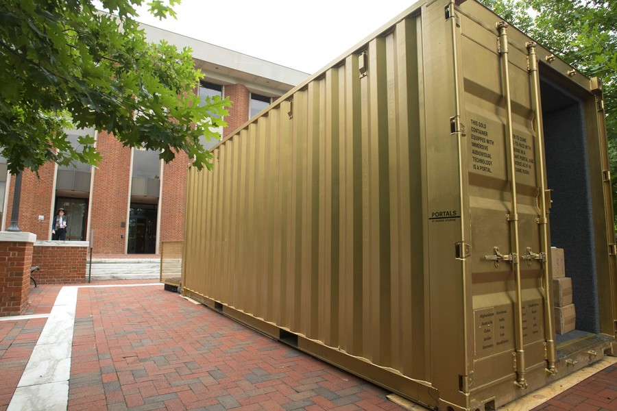 Gold shipping container in front of brick academic building