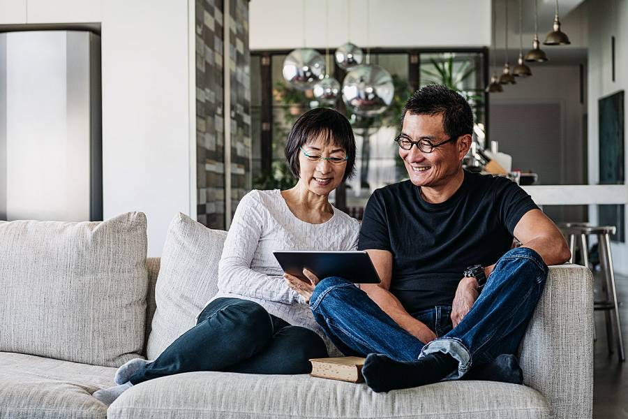 Smiling older couple sitting on a couch looking at a tablet