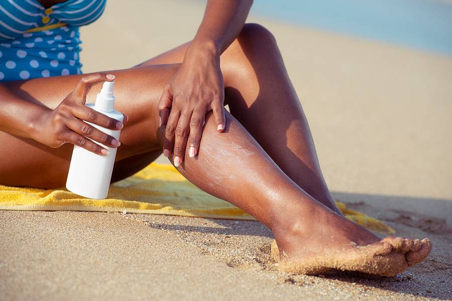 Woman putting sunscreen on her legs
