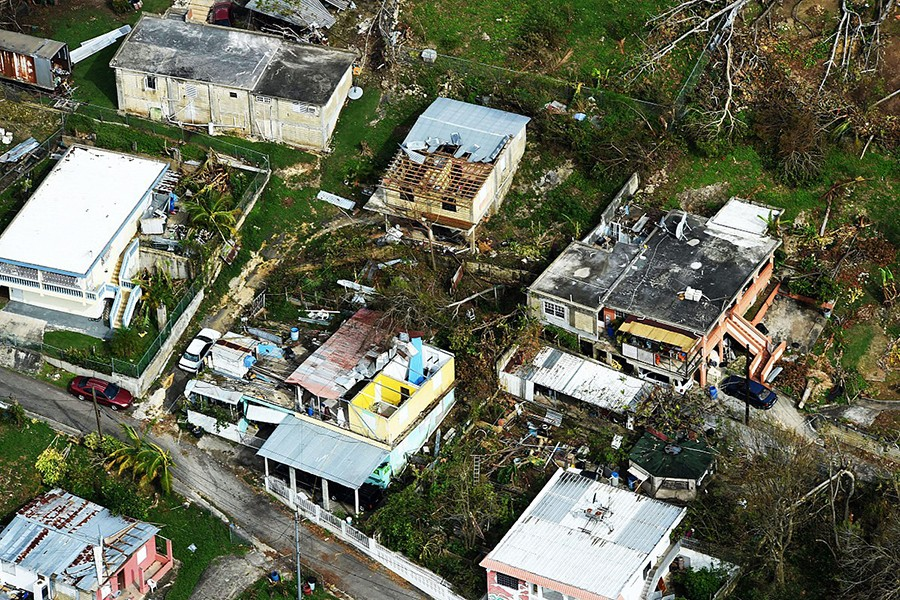 The roofs of houses are torn off, and downed trees and debris litters the ground