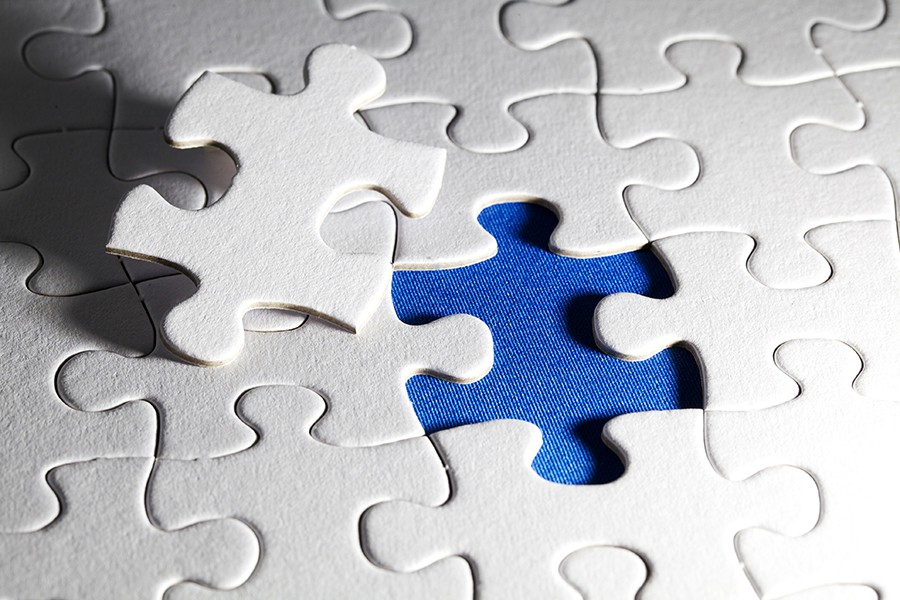 White puzzle pieces with on piece removed to reveal blue underneath