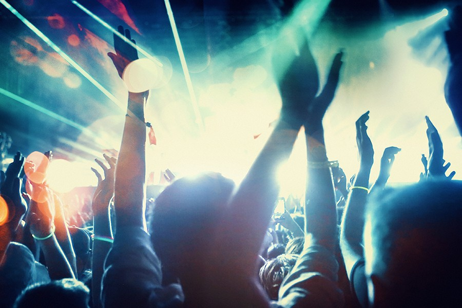 Concertgoers in front of concert stage with strobe lights