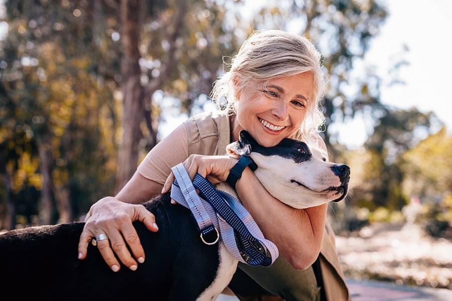 Smiling senior woman hugging dog