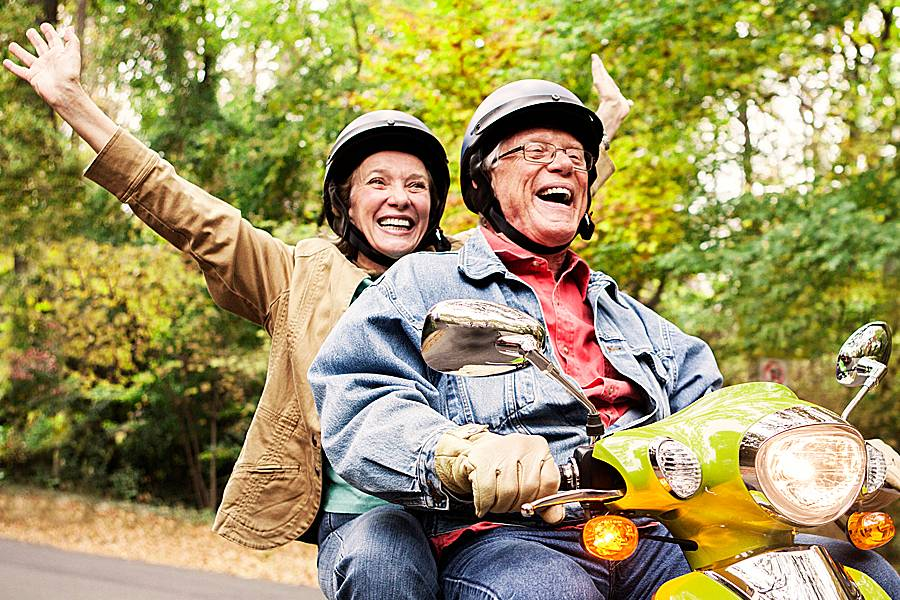 Happy older couple riding a motorcycle