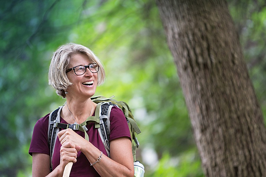 A happy middle-aged woman in hiking gear is enjoying the woods