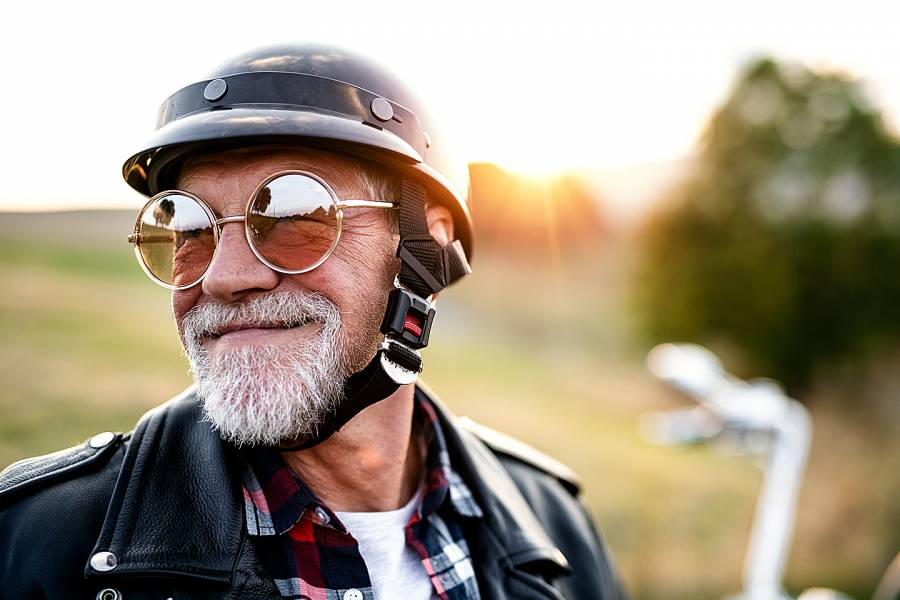 Senior man with beard, sunglasses, and helmet on a motorcycle