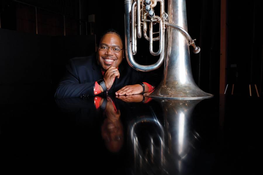 Richard A. White sits next to his tuba