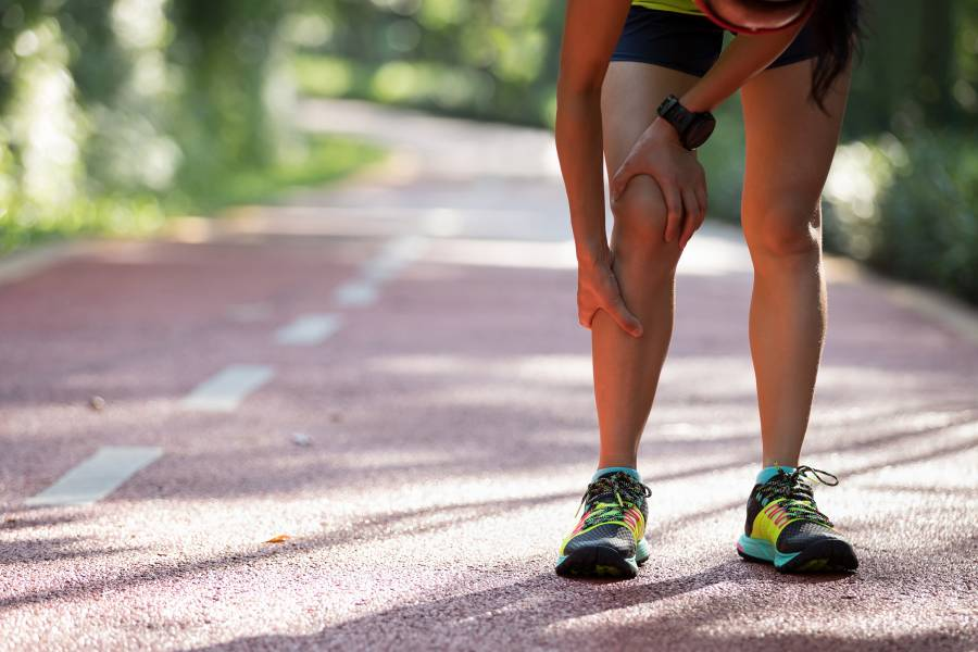 A runner pauses and holds her leg in pain