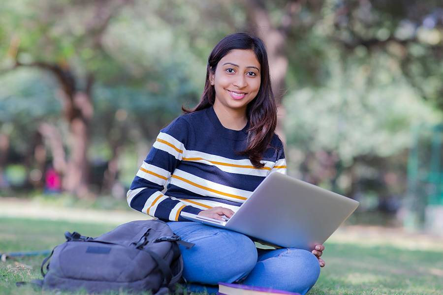 Young woman with laptop sitting on school campus