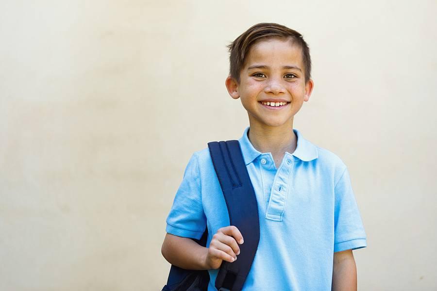 Smiling young boy in blue uniform shirt