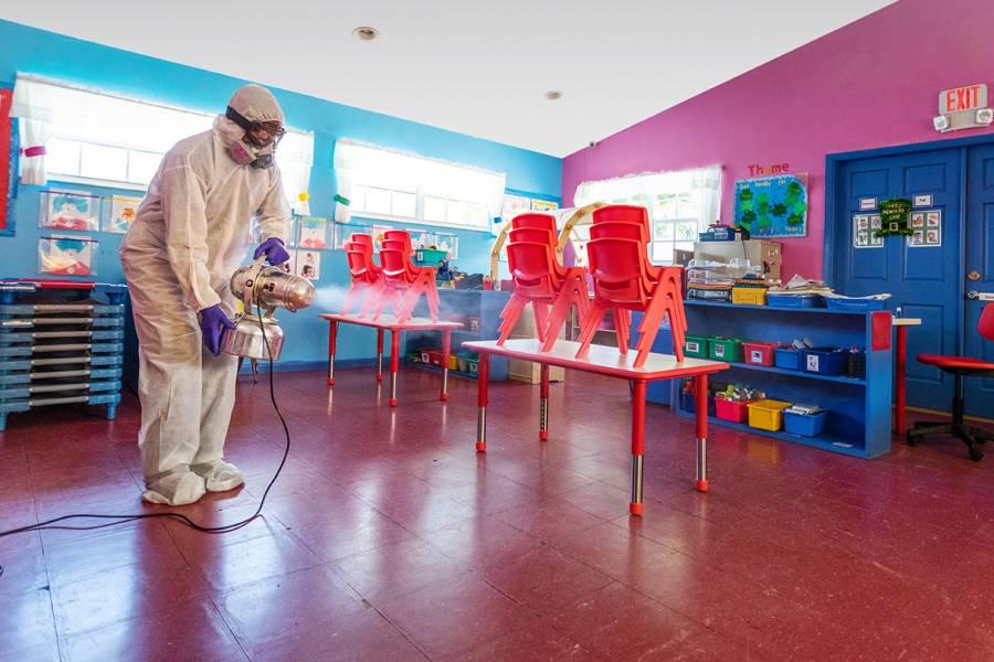 A masked custodian cleans a classroom