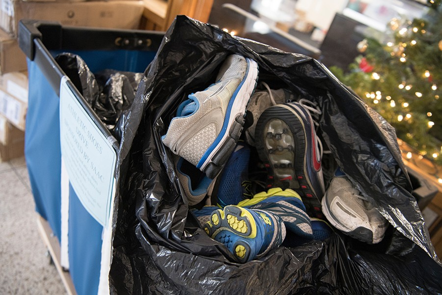 A rolling bin contains a giant black trash bag filled with athletic shoes