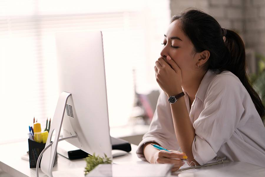 Woman yawning in front of her computer