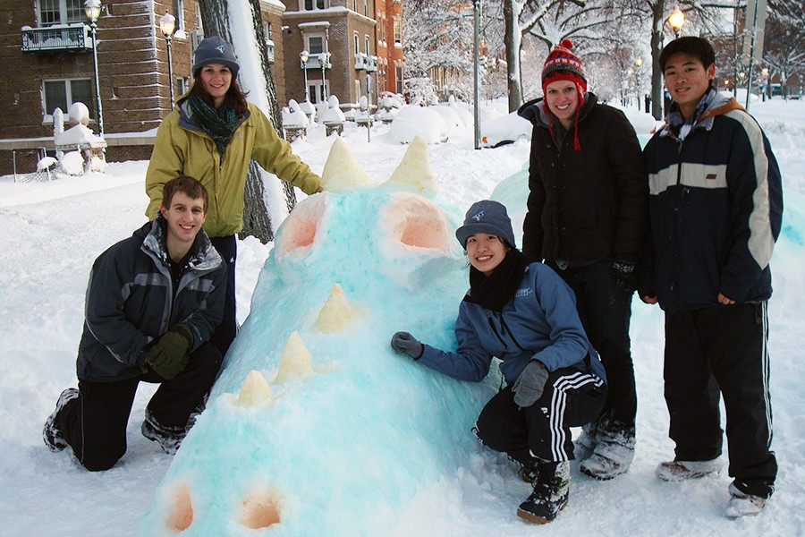 A group of students pose beside a snow dragon dyed blue with orange eyes