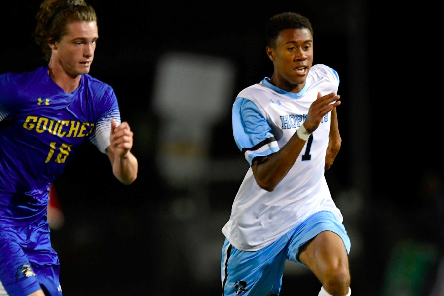 Two soccer players chase the ball