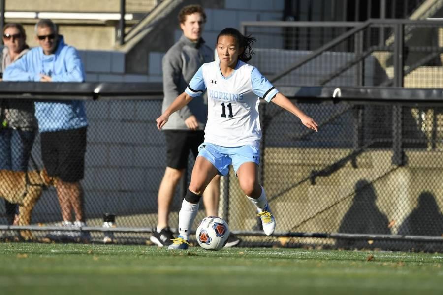 Johns Hopkins women's soccer player dribbles