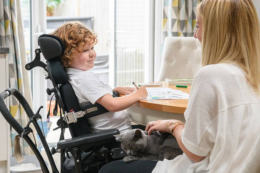 Boy in a wheelchair at a table with his mother