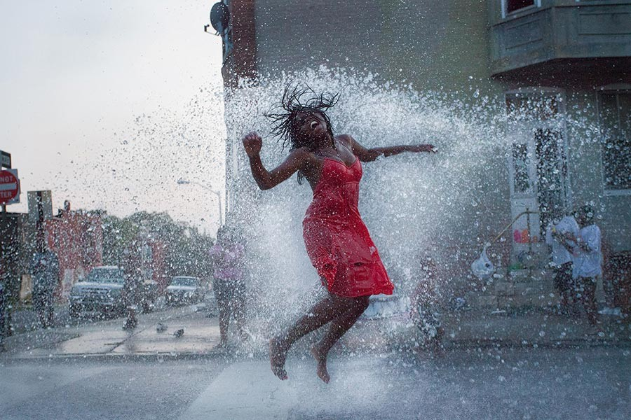 Woman jumping in stream of a fire hydrant