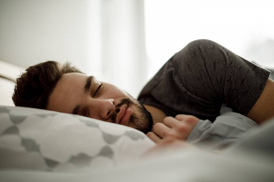 Man sleeping peacefully in bed at home