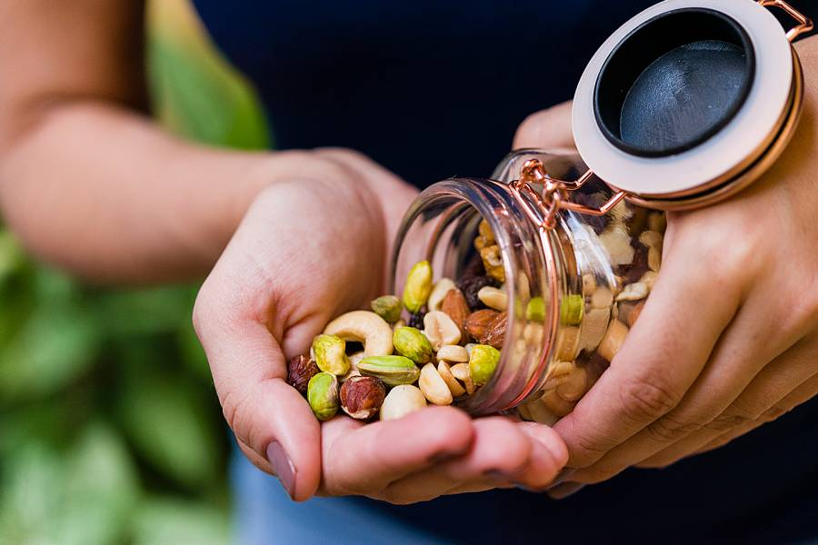 A hand holding nuts pouring from a jar