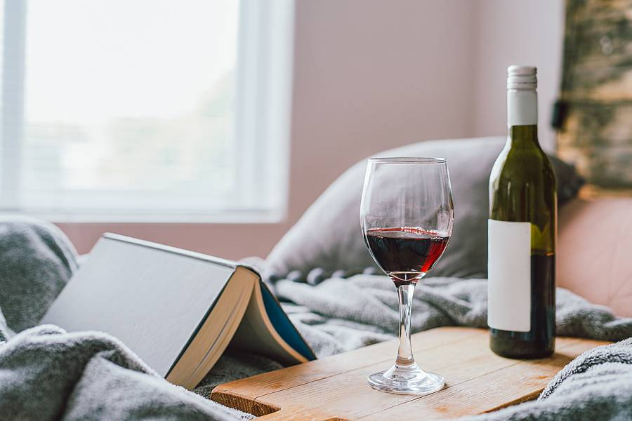 Bottle of wine and a glass near an open book on a bed