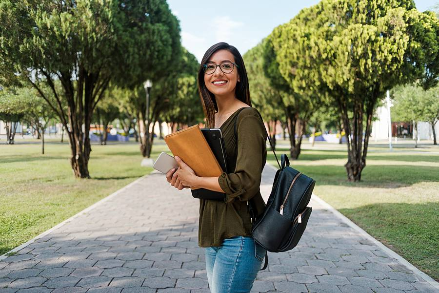 Smiling young woman holding books on a college campus