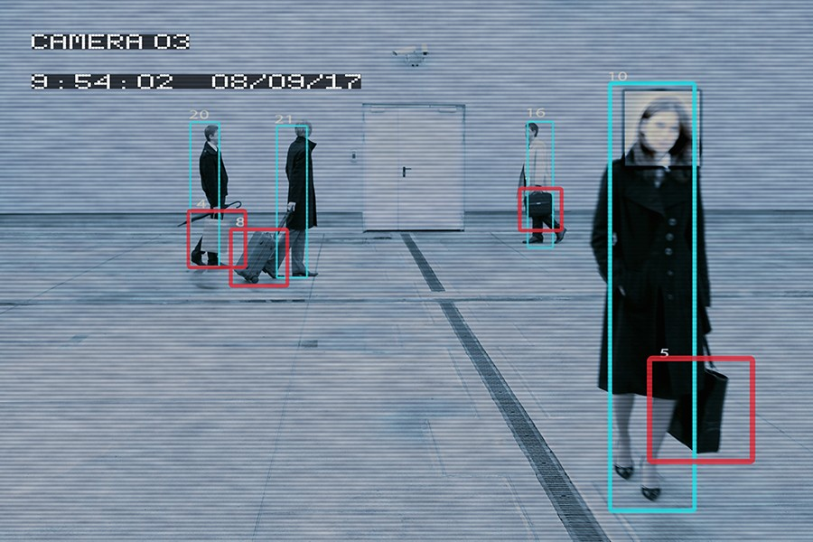 Security camera image with blue and red boxes overlaying people and bags