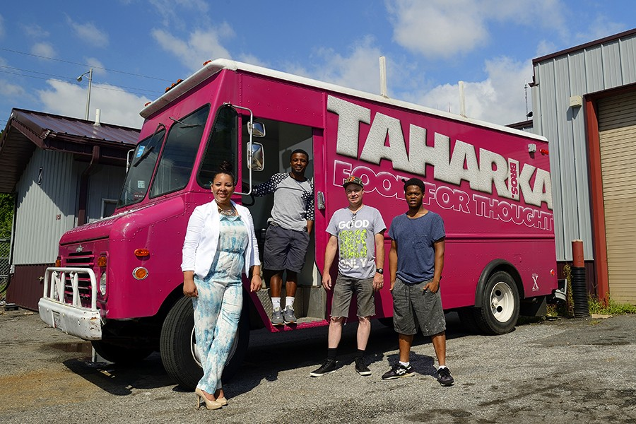 Four people pose in front of magenta Taharka Brothers ice cream truck