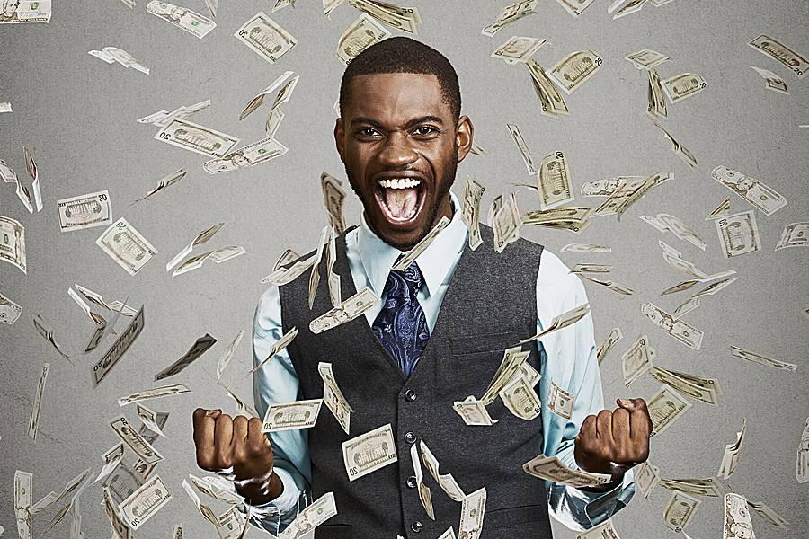 Young man fist pumps with money raining on him