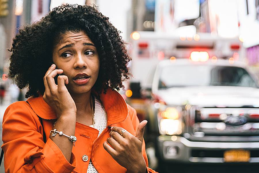 Concerned-looking woman on phone near cars in big city