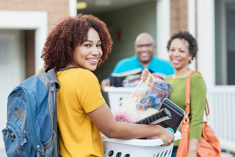 Young woman and her parents moving her belongings into a dorm