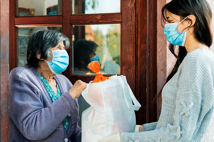 Young woman delivering groceries to an elderly woman, both of them wearing facial masks