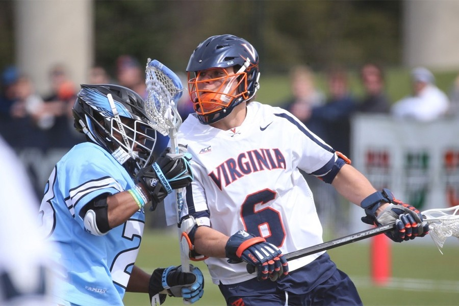 A Virginia lacrosse player goas to the goal against a Hopkins defender
