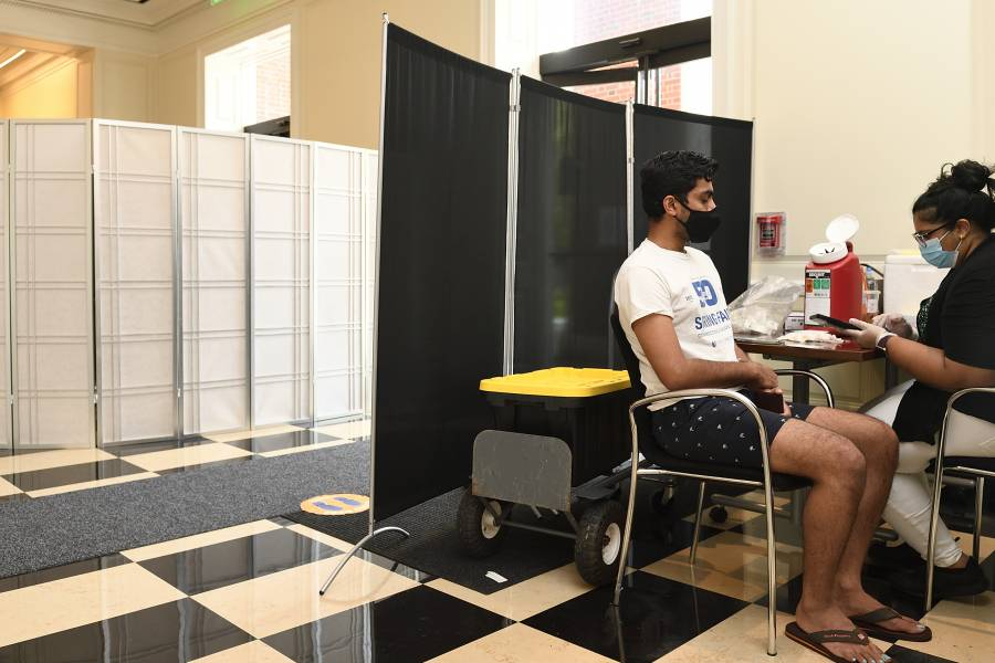 A student gets vaccinated at a free Johns Hopkins vaccine clinic