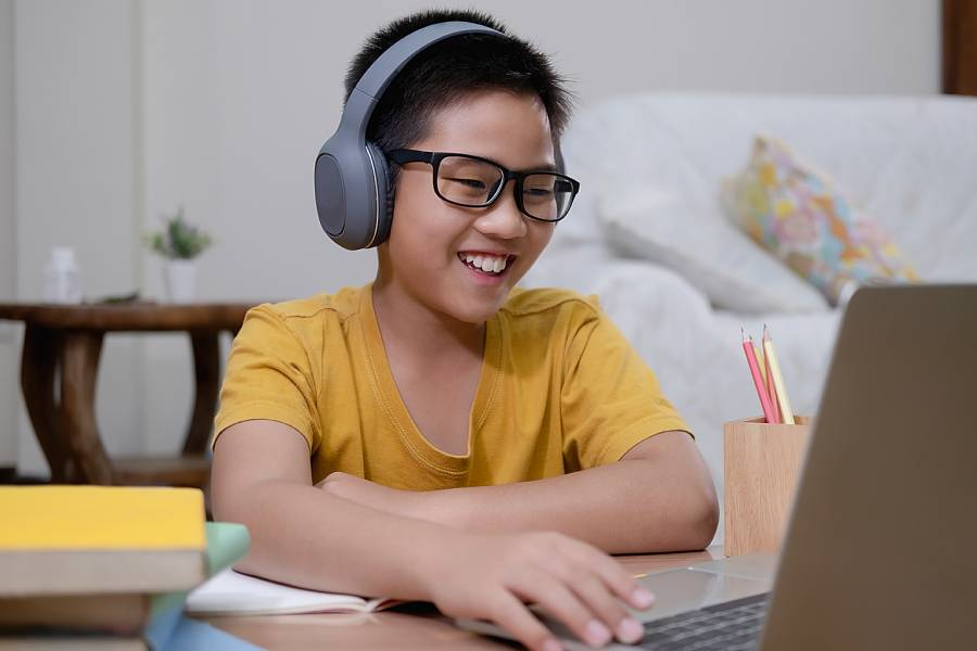 Young boy wearing headphones and working on computer