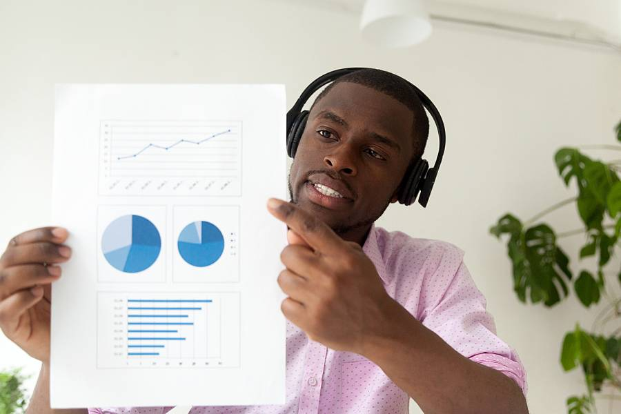 Young man wearing headphones and holding chart up to camera