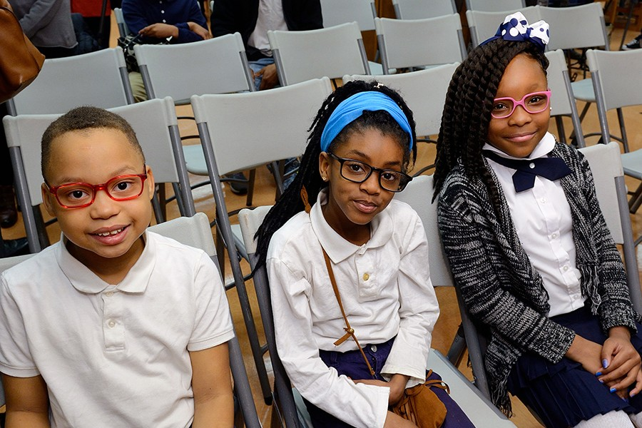 Three children wearing glasses smile for the camera