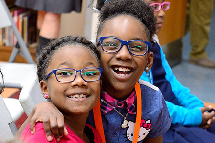 Two little girls smile in brand new glasses