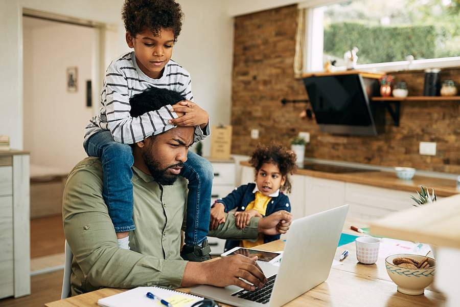 Man working on laptop while two young children try to get his attention