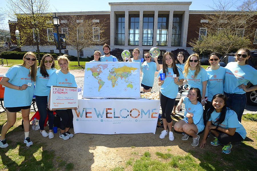 Students in blue t-shirts pose with map, globes, and