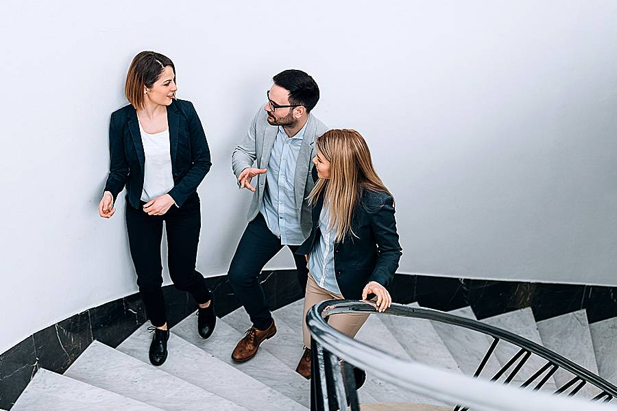 Three people talk while walking up stairs
