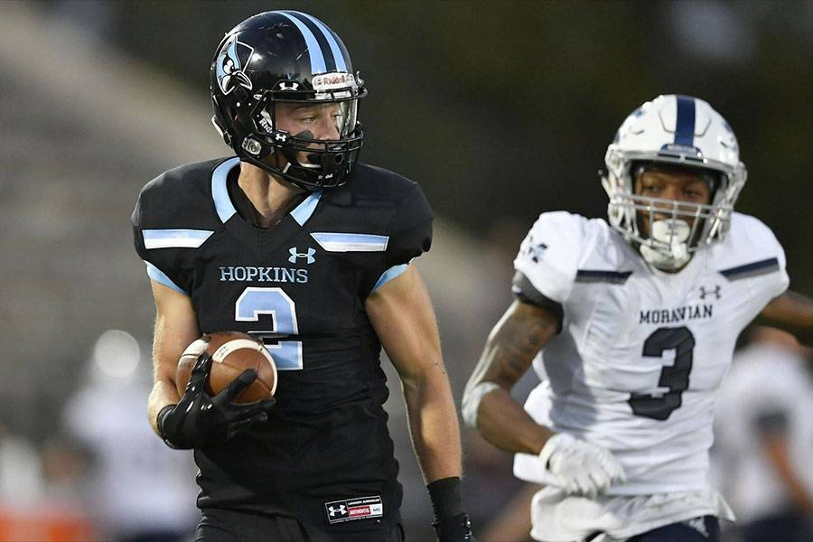 Hopkins football player races away from defender en route to the end zone