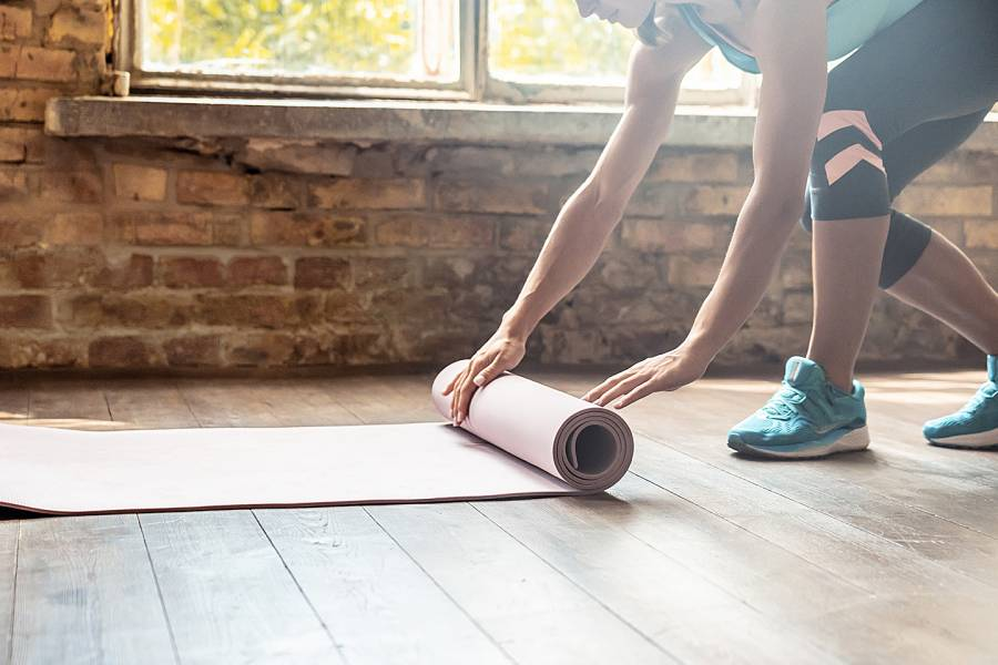 Woman laying exercise mat on the floor of her home