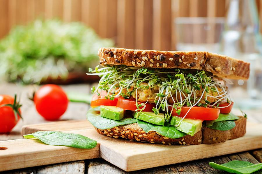 Sandwich of tomato, spinach, avocado, and chickpeas burger on whole grain bread