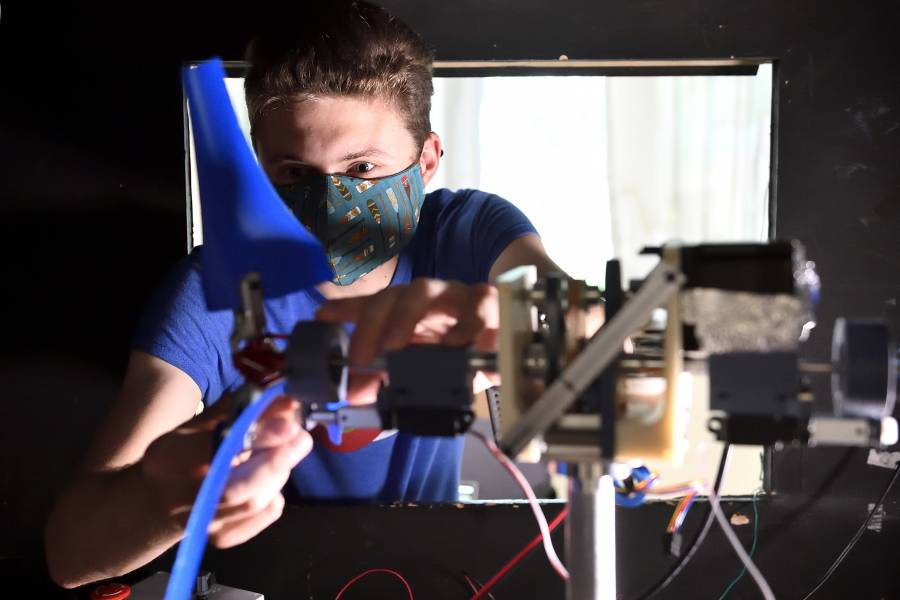 A student makes adjustments to a turbine in a test wind tunnel
