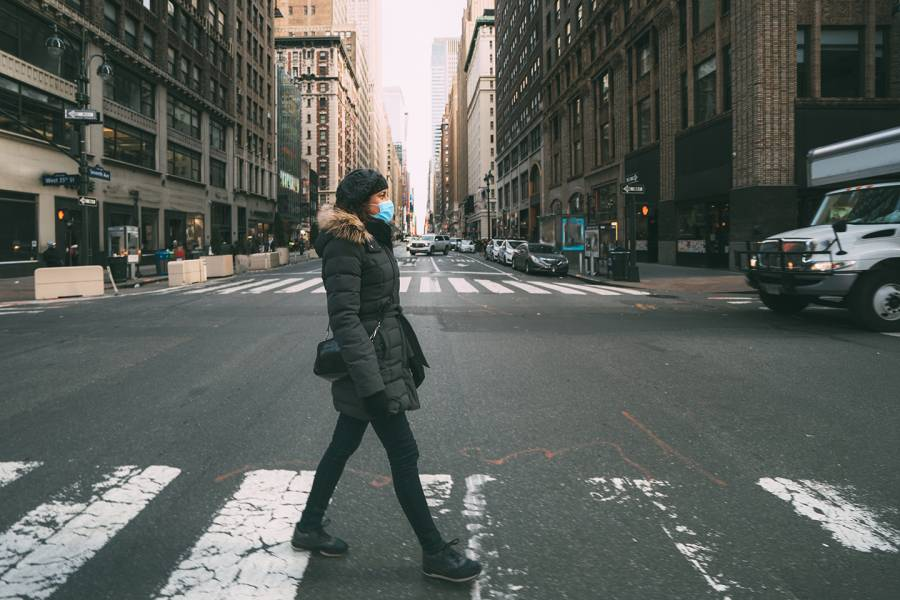 Woman in winter coat crosses street in NYC